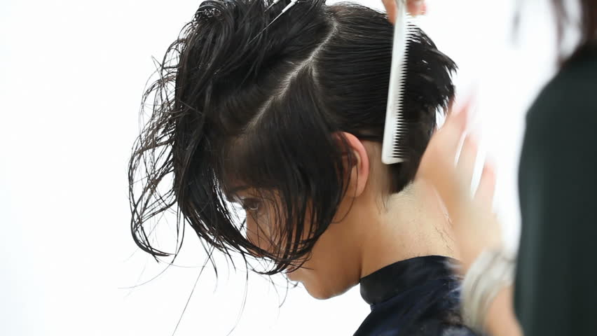 Young woman cutting hair at the hairdresser isolated on white background. Hairstylist cuts the hair to a young girl with a professional scissors.