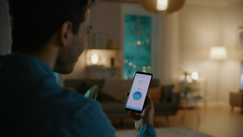 Young Handsome Man Gives a Voice Command to a Smart Home Application on His Smartphone and Lights in the Room are Being Turned On. It's a Cozy Evening. #1023495715