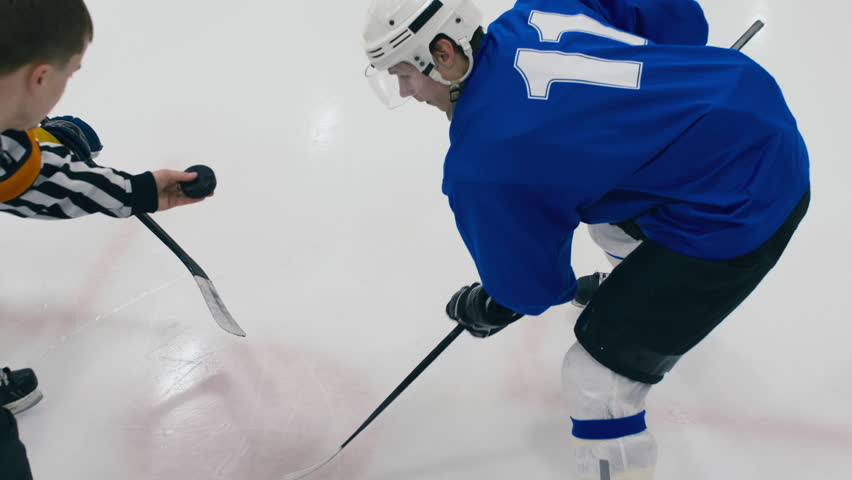 High angle shot of referee throwing puck to face-off on ice hockey game | Shutterstock HD Video #1023504589