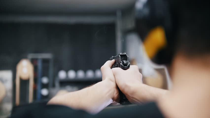 Shooting gallery. A young man shooting with a firearms. A smoking gun