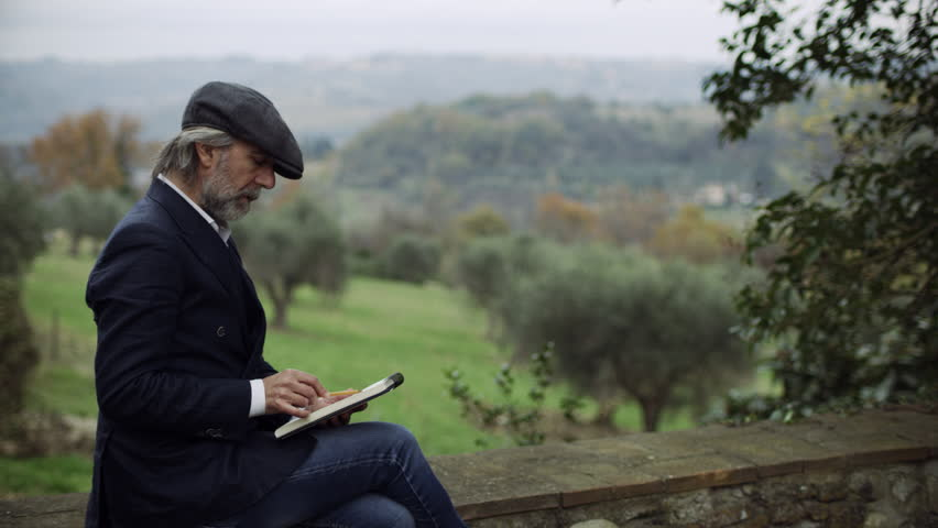 Wide shot on 8k helium RED camera. Content Italian man sitting on a stone wall, writing in his book and looking out at the beautiful scenic landscape in Tuscany, on soft overcast day.