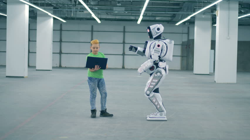 Boy controls cyborg while using laptop. Concept of future. | Shutterstock HD Video #1023534760