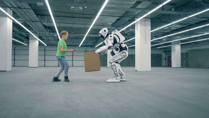 A child controls robot while it takes a box. Futuristic humanoid robot. | Shutterstock HD Video #1023534790
