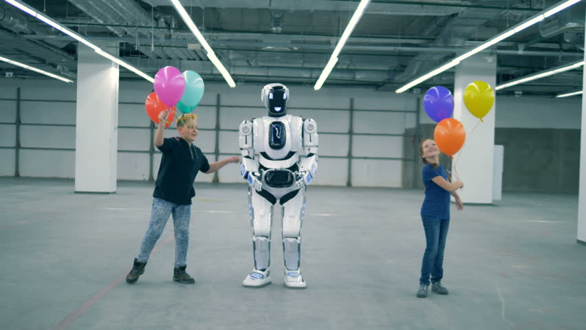Android and children dance with balloons. Modern cyborg with children | Shutterstock HD Video #1023534979