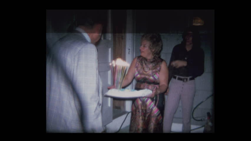 Man blows out candles on 50th Birthday cake 1971