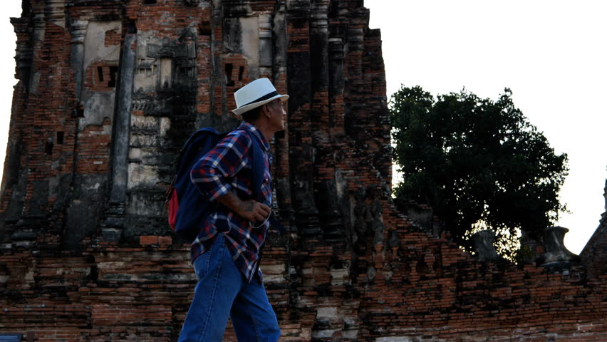 Senior man Asian with backpack are walking at Wat Chaiwatthanaram. Ancient and historical attractions and one of the most important archaeology of Ayutthaya province thailand. Travel, Tourist Concept #1023549997