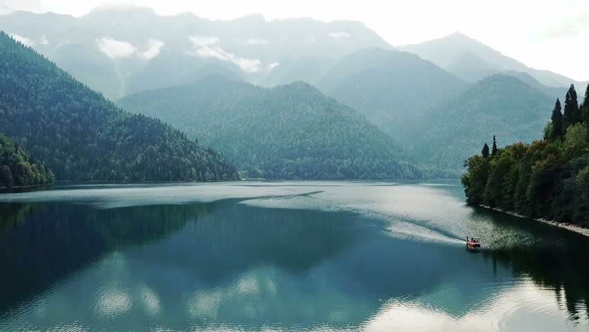 Mountain lake with turquoise water and green trees. Reflection in the water. Beautiful spring landscape with mountains, forest and lake. Aerial View. Drone shot over a beautiful mountain forest lake | Shutterstock HD Video #1023565975