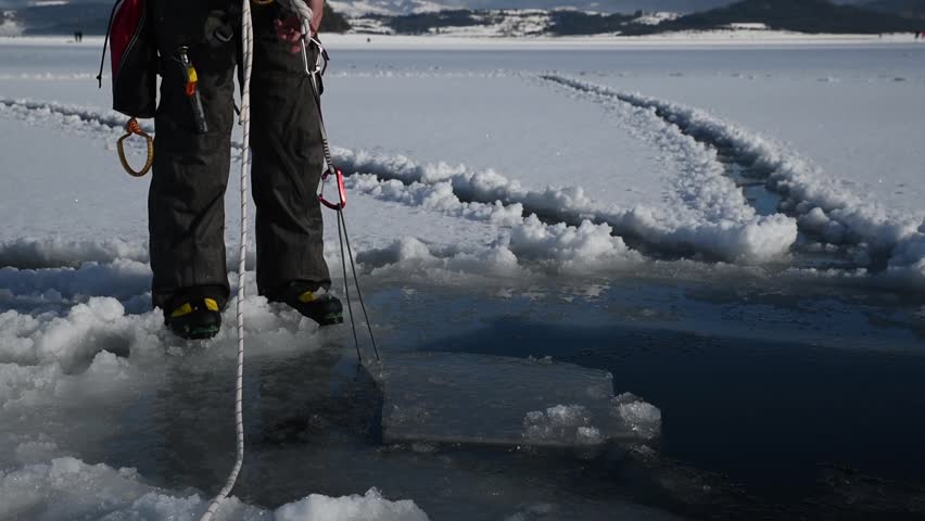 Caucasian man pulling cut piece ice from the frozen lake. Selective focus  | Shutterstock HD Video #1023568372