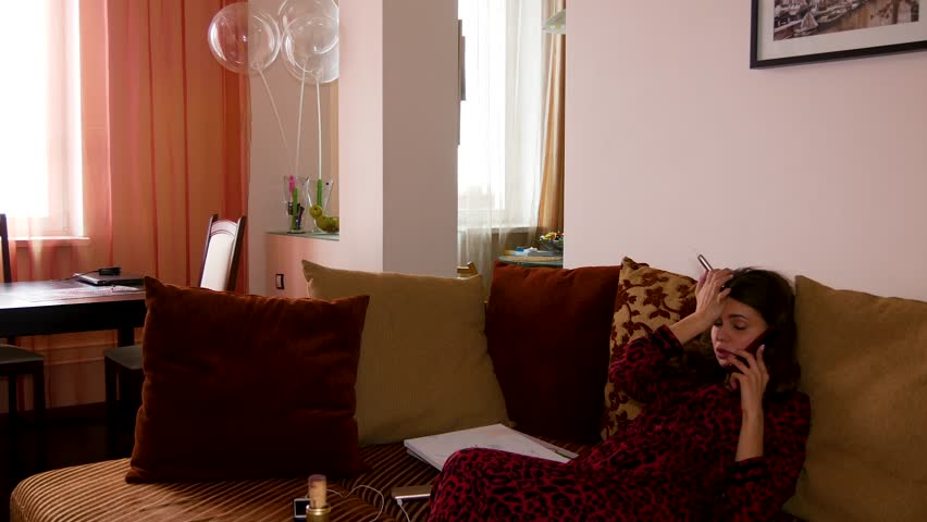 A young girl sitting on the couch and talking on the phone. | Shutterstock HD Video #1023571579