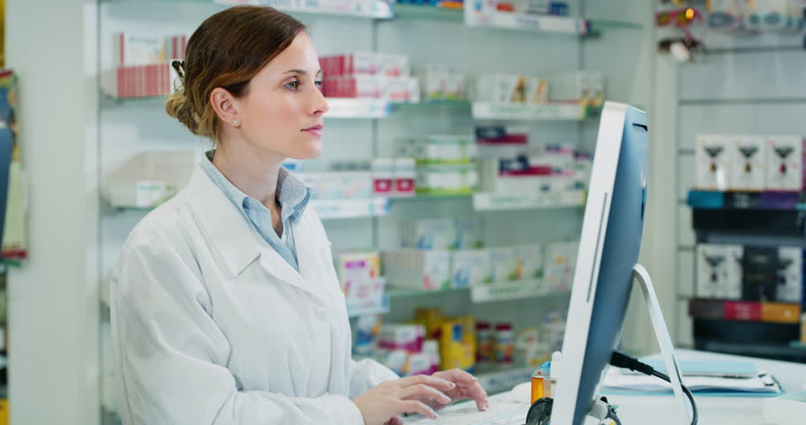 Slow motion of young woman pharmacist searching medicine for a patient  in computer in a drugs store. Shot in 8K. Concept of profession, medicine and healthcare, medical education, pharmaceutical sect
