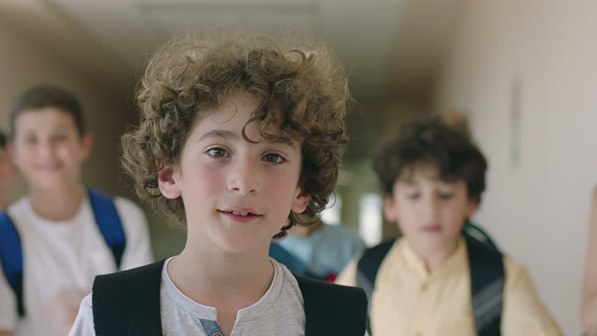 Close up portrait of beautiful , attractive , caucasian curly hair boy . Young boy looking and smiling on the camera inside school with friends . Portrait of children looks and smiles positive mood . #1023585535