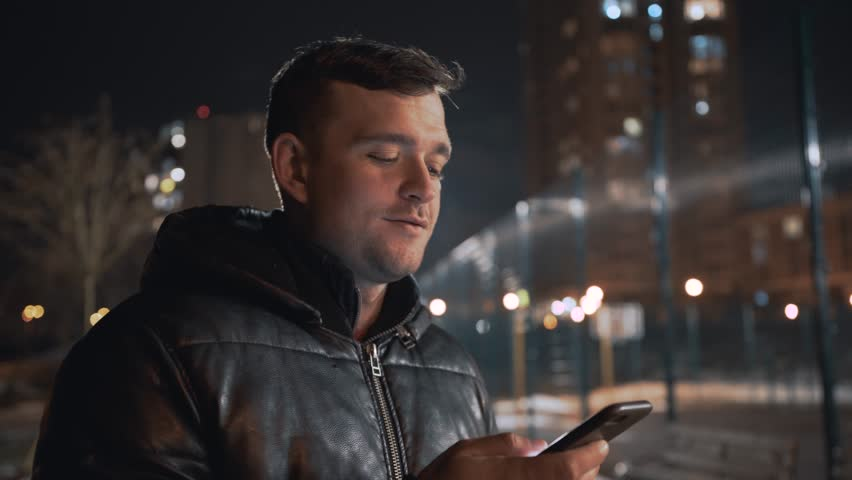 Man calling and talking on smart phone with mimic emotions smiling and sad at night city with light on background | Shutterstock HD Video #1023585805