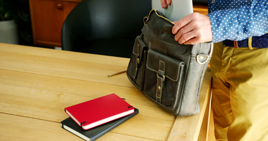 Close up of male entrepreneur putting his laptop, notebooks and journal in his satchel. Design professional is packing up after a hard day at his modern start up office. Shot on RED Camera Royalty-Free Stock Footage #1023599500