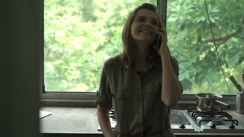 Young happy woman talking on cellphone by the window in kitchen | Shutterstock HD Video #1023623722