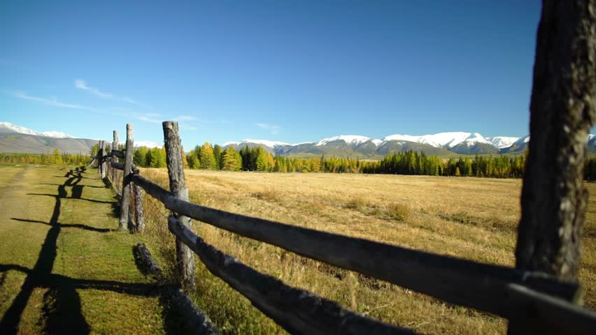 Evening in the mountains. the sun is low, beautiful light, in the foreground a wooden fence, a snow-covered mountain in the background.   Shutterstock HD Video #1023634237