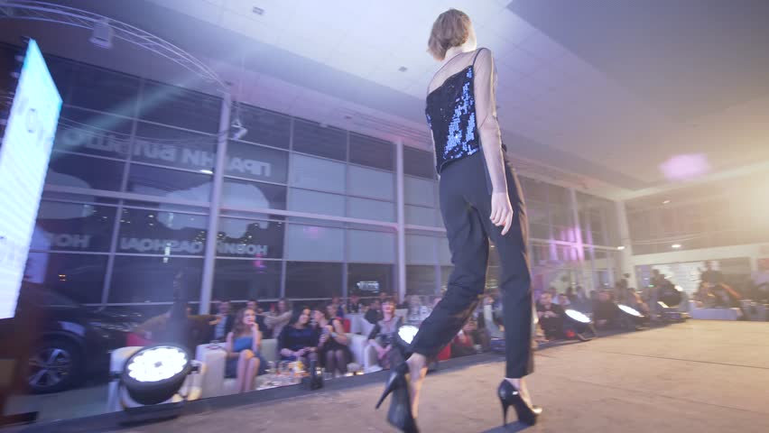 KHERSON, UKRAINE - DECEMBER 01, 2018: professional model girl in high heels into stylish black suit defile on catwalk at fashion event into floodlight | Shutterstock HD Video #1023636235