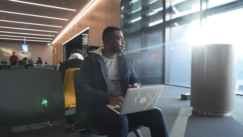 Black man waiting for his flight in terminal New Istanbul airport and using laptop. African american man working while waiting for landing to the plane. Shooting in January 2019 Turkey Istanbul  | Shutterstock HD Video #1023636409
