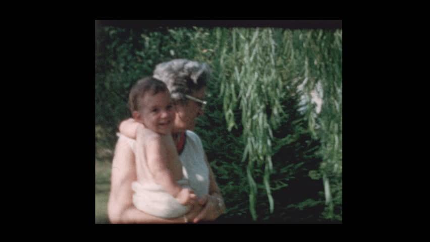 Portrait of elderly grandmother holding baby grandson 1961