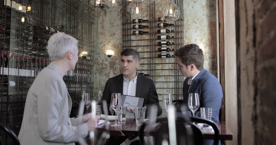 Business executives having a working lunch in a restaurant | Shutterstock HD Video #1023646090