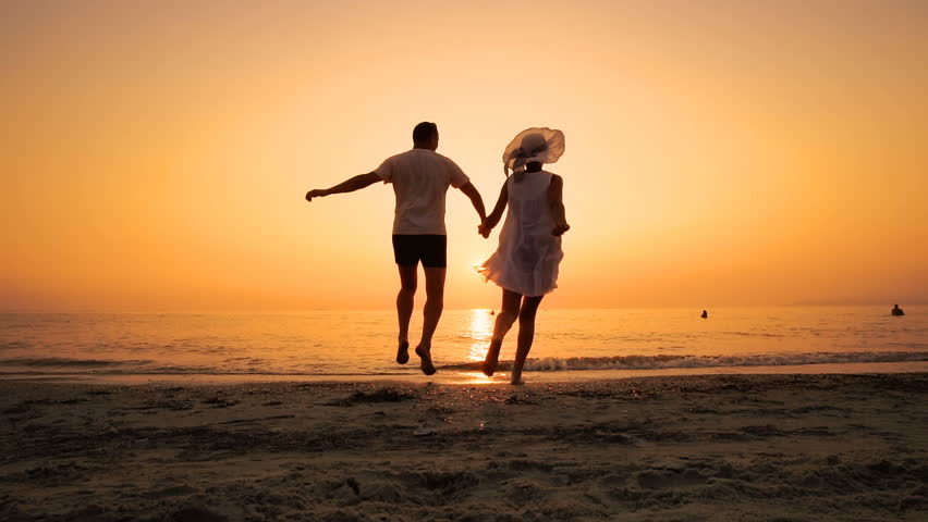 Romantic couple running on beach at sea sunset holding hands and jumping in slow motion. Man takes woman in air and turning her around. Concept of love and happiness