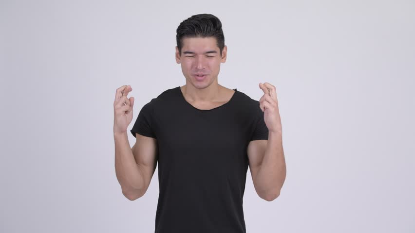 Young handsome multi-ethnic man wishing with fingers crossed   Shutterstock HD Video #1023660592