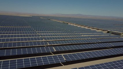 Aerial footage of hundreds solar energy modules or panels rows along the dry lands at Atacama Desert, Chile. Huge Photovoltaic PV Plant in the middle of the desert from an aerial drone point of view