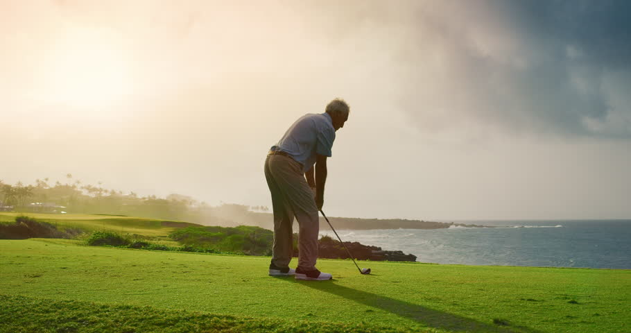Handsome older golfer swinging and hitting golf ball on beautiful course with ocean at sunset, slow motion