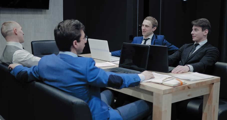 Young partners communicate in a meeting. Colleagues are sitting in a modern office at a table with laptops and talking. | Shutterstock HD Video #1023685204