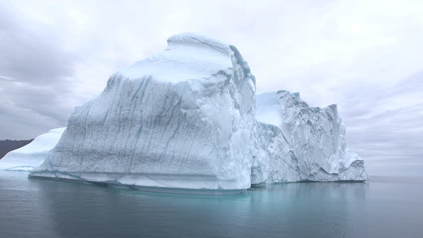 Moving shot from a boat turning around a big iceberg in the middle of the Arctic Ocean, Greenland Royalty-Free Stock Footage #1023687982