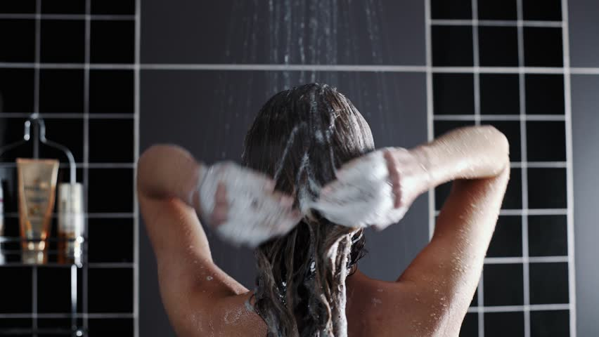 Woman washes her hair with shampoo in the shower with, hair care, ceratin mask, rinse shampoo and balm, strong hair, washing hair | Shutterstock HD Video #1023693790