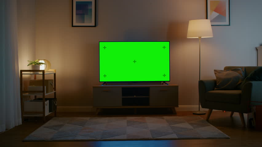 Zoom In Shot of a TV with Horizontal Green Screen Mock Up. Cozy Evening Living Room with a Chair and Lamps Turned On at Home. | Shutterstock HD Video #1023697372