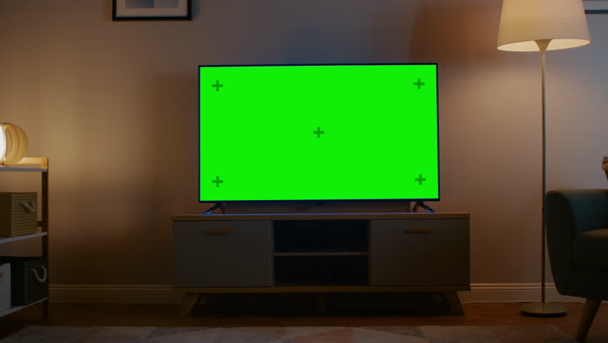 Zoom Out Shot of a TV with Horizontal Green Screen Mock Up. Cozy Evening Living Room with a Chair and Lamps Turned On at Home. | Shutterstock HD Video #1023697378