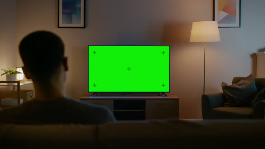Young Man in Glasses is Sitting on a Sofa and Watching TV with Horizontal Green Screen Mock Up. It's Evening and Room at Home Has Working Lamps. #1023697384