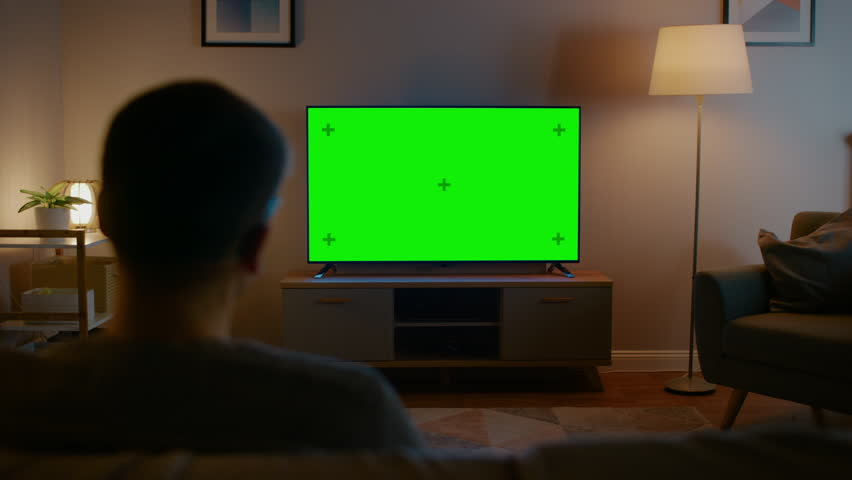 Young Man in Glasses is Sitting on a Sofa and Watching TV with Horizontal Green Screen Mock Up. It's Evening and Room at Home Has Working Lamps. #1023697390