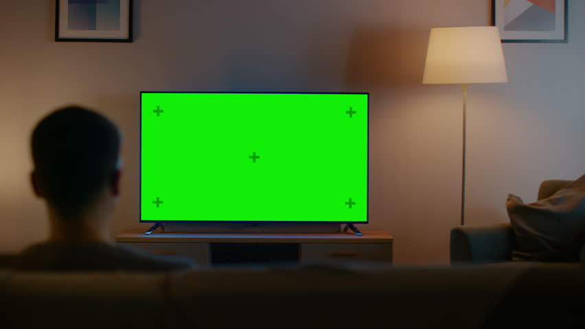 Young Man in Glasses is Sitting on a Sofa and Watching TV with Horizontal Green Screen Mock Up. It's Evening and Room at Home Has Working Lamps. | Shutterstock HD Video #1023697393