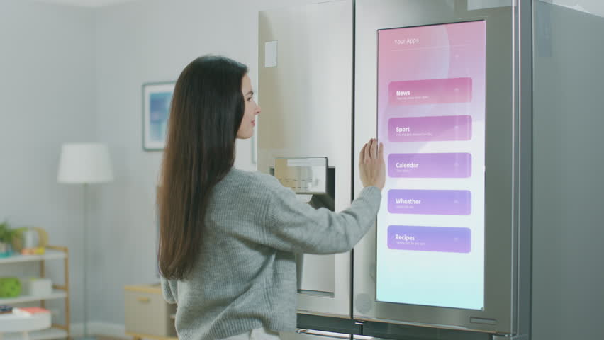 Beautiful Young Girl Walks Over to a Refrigerator While Drinking Her Morning Coffee. She is Checking the Weather Forecast and a To Do List on a Smart Fridge at Home. Kitchen is Bright and Cozy. Royalty-Free Stock Footage #1023697405
