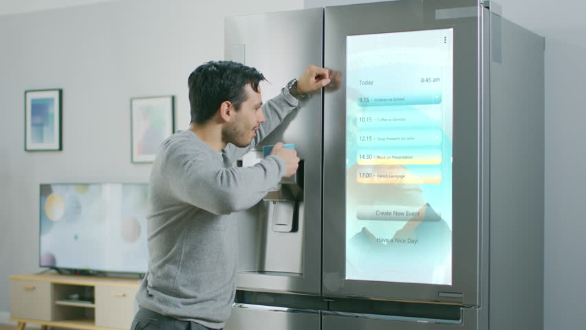 Handsome Young Man Walks Over to a Refrigerator While Drinking His Morning Coffee. He is Checking a To Do List on a Smart Fridge at Home. Kitchen is Bright and Cozy. Royalty-Free Stock Footage #1023697408