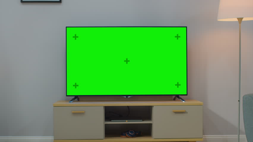 Zoom Out Shot of a TV with Horizontal Green Screen Mock Up. Cozy Living Room at Day Time with a Chair and Lamps Turned On at Home. | Shutterstock HD Video #1023697468