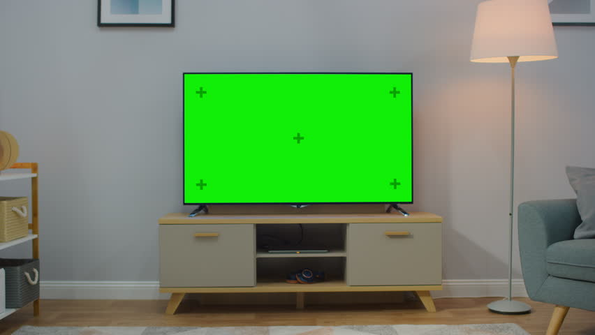 Zoom Out Shot of a TV with Horizontal Green Screen Mock Up. Cozy Living Room at Day Time with a Chair and Lamps Turned On at Home. | Shutterstock HD Video #1023697471
