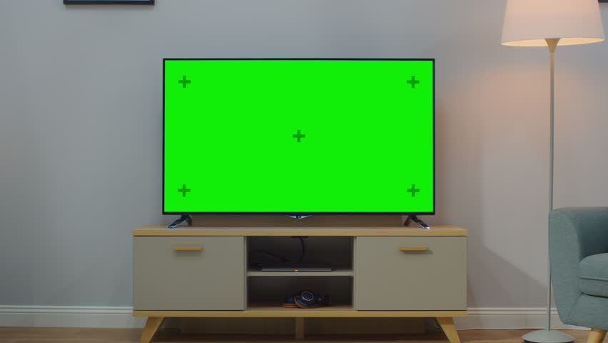 Zoom In Shot of a TV with Horizontal Green Screen Mock Up. Cozy Living Room at Day Time with a Chair and Lamps Turned On at Home. | Shutterstock HD Video #1023697474