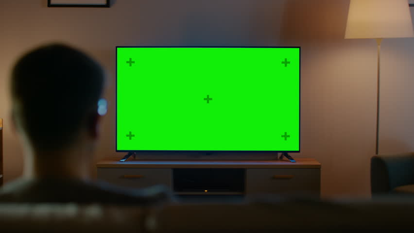 Young Man in Glasses is Sitting on a Sofa and Watching TV with Horizontal Green Screen Mock Up. It's Evening and Room at Home Has Working Lamps. | Shutterstock HD Video #1023697486