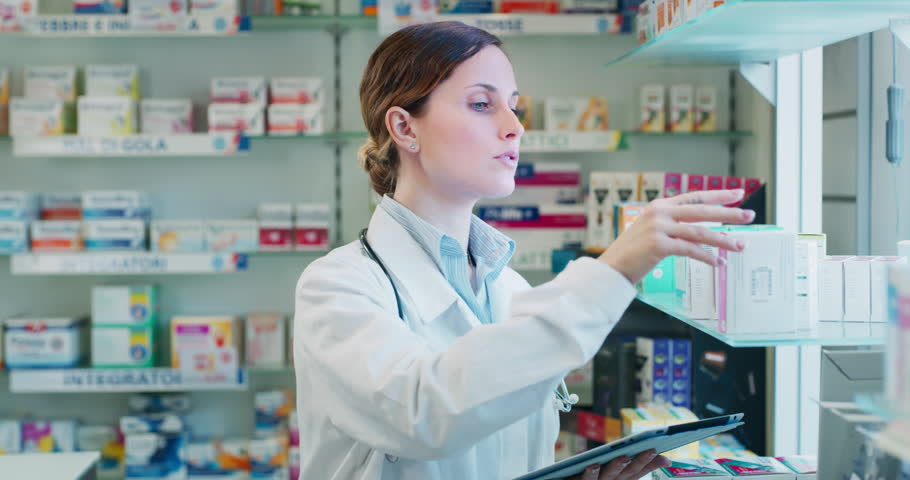 Slow motion of an young woman pharmacist consultant checking medicines on the shelf of drug store. Shot in 8K. Concept of profession, medicine and healthcare, medical education, pharmaceutical sector