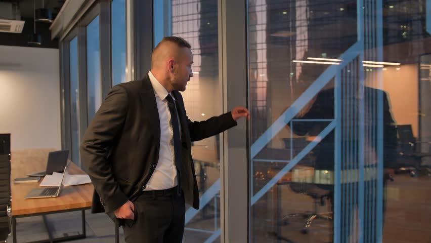 Successful businessman in suit standing in office with hands in pockets, CEO. Businessman from the back in front of a city view on the window. 4k UltraHD slow motion middle shot. | Shutterstock HD Video #1023706834