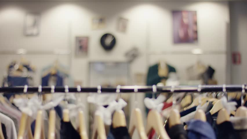 Pretty young woman walks by rack of clothes in a clothing shop and take a quick look on a clothes | Shutterstock HD Video #1023715843