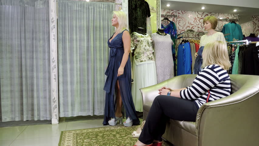 Fashion and clothing. Mid-adult attractive blonde woman trying on dress, shoes and women's hat in a dress shop. 4K | Shutterstock HD Video #1023720112