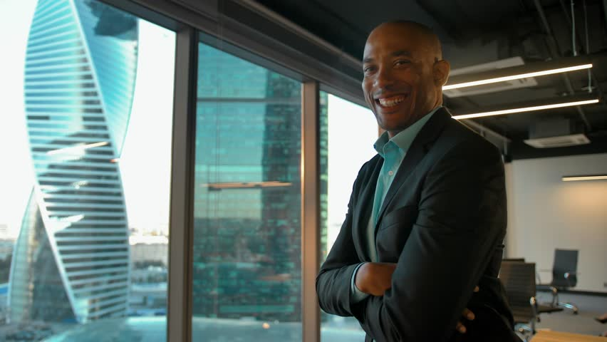 African american boss standing near huge modern office window and smiles. Business district background. Epic slow motion glidetrack movement. | Shutterstock HD Video #1023720286