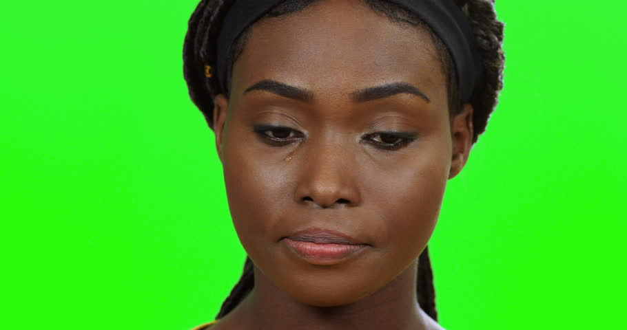 Portrait of the young African American woman crying in front of the camera on the green screen background. Close up of the face with tears. Chroma key.