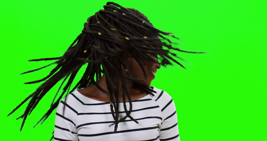 Close up of the young cheerful African American woman dancing and waving her head with long braids, then smiling on the alpha channel green wall.