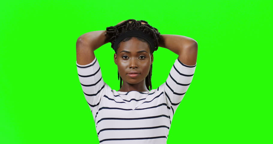 Portrait of the pretty joyful young African American girl lifting her hair with pigtails up, then letting go and smiling happily to the camera on the green screen background. Chroma key.