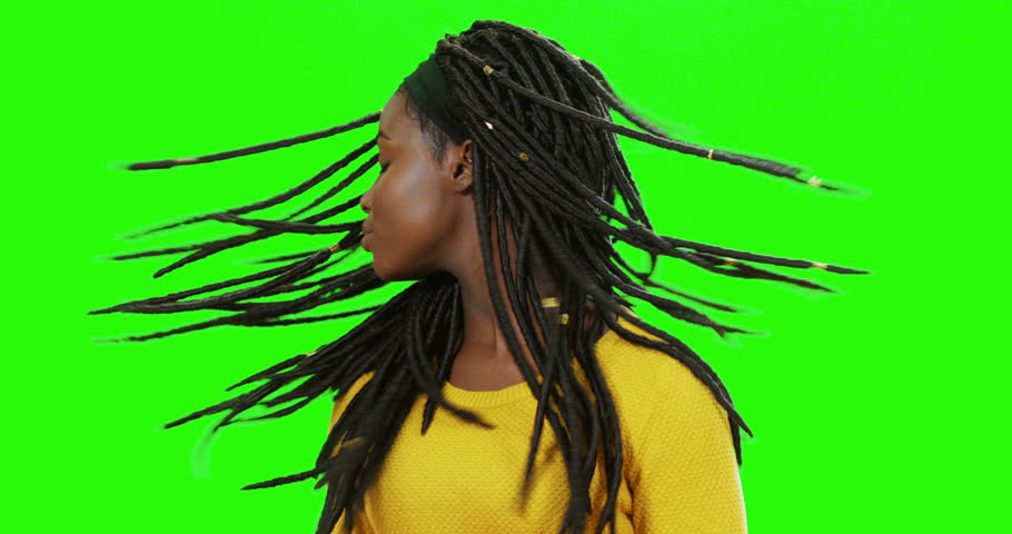 Close up of the young cute African American girl with pigtails waving her head and smiling on the chroma key background.